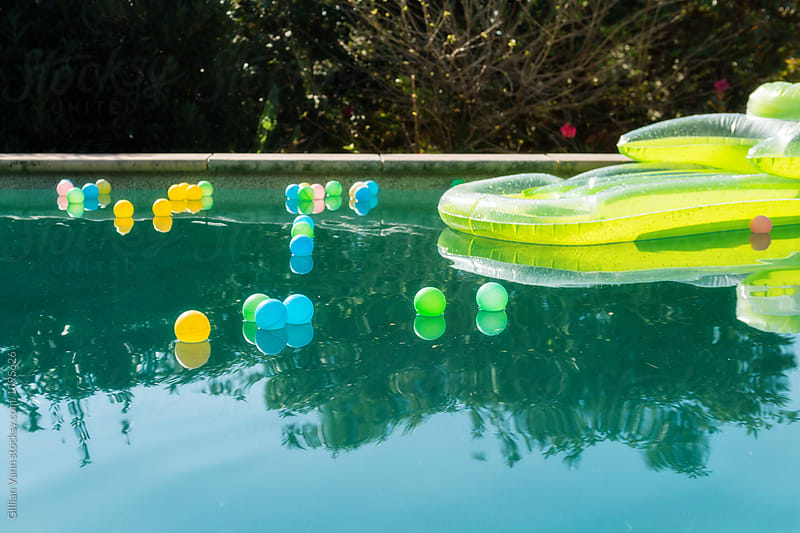 lilo and pool balls floating on the pool by Gillian Vann for Stocksy United