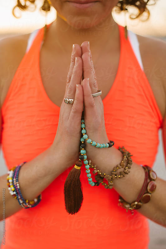 Womans hands in prayer pose holding yoga beads. by Kate Daigneault for Stocksy United