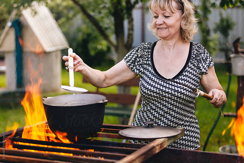 Mature woman cooking food on open fire on bbq by Ilya for Stocksy United