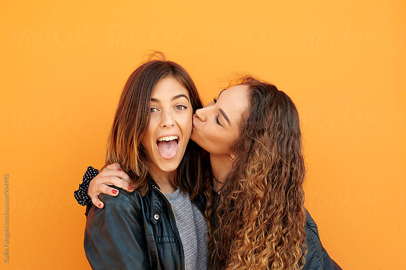 Cheerful girl sticking out tongue while her girlfriend kissing her in cheek by Guille Faingold for Stocksy United