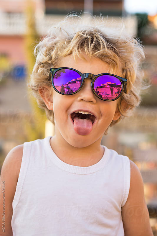 Little boy with sunglasses sticking out his tongue by ACALU Studio for Stocksy United