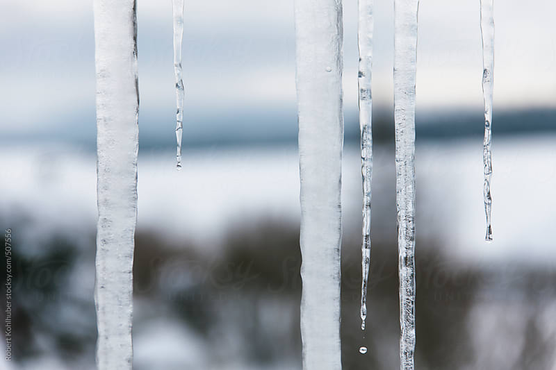Large icicles on window by Robert Kohlhuber for Stocksy United