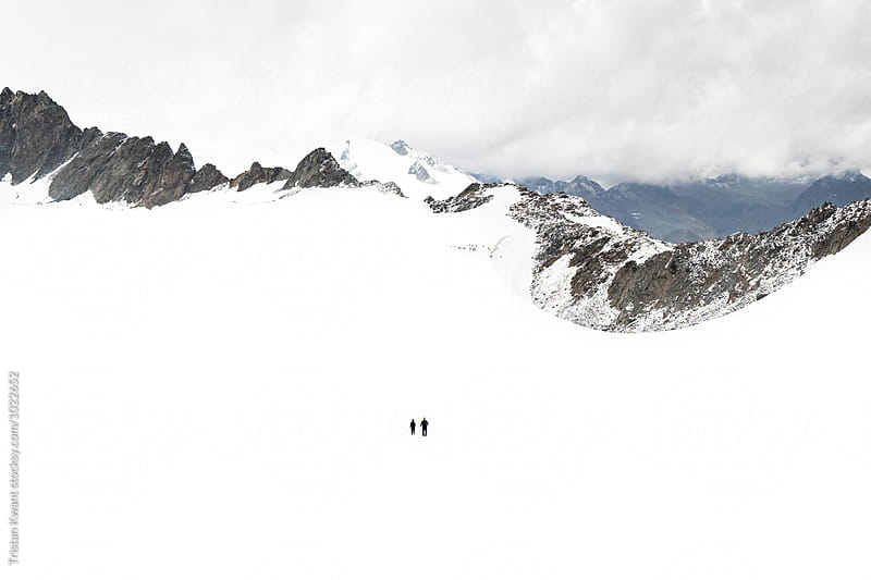 Two climbers walking on a glacier in the snow. by Tristan Kwant for Stocksy United
