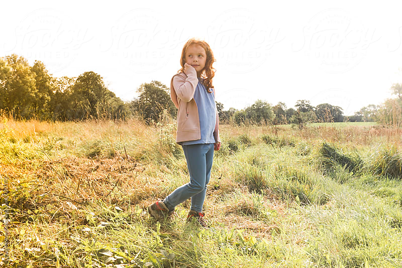 Seven year old girl walking in the countryside by Craig Holmes for Stocksy United