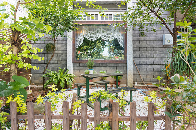 Designed backyard with trees, plants, wooden table and chairs by Lawren Lu for Stocksy United