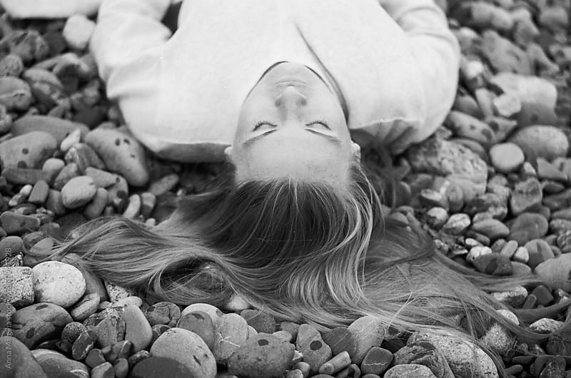A black and white film portrait of a young beautiful  woman lying on the rocks by Anna Malgina for Stocksy United