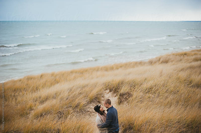 Couple hugging on sand dunes at lake on cold windy winter day by Daring Wanderer for Stocksy United