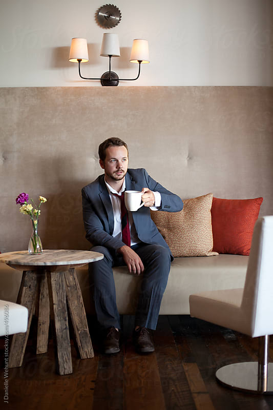 man in business suit drinking coffee by J Danielle Wehunt for Stocksy United