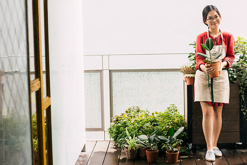 Florist Holding potted flowers. by Lumina for Stocksy United