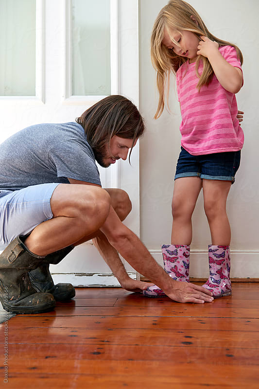 father helps daughter with her shoes  by Daxiao Productions for Stocksy United