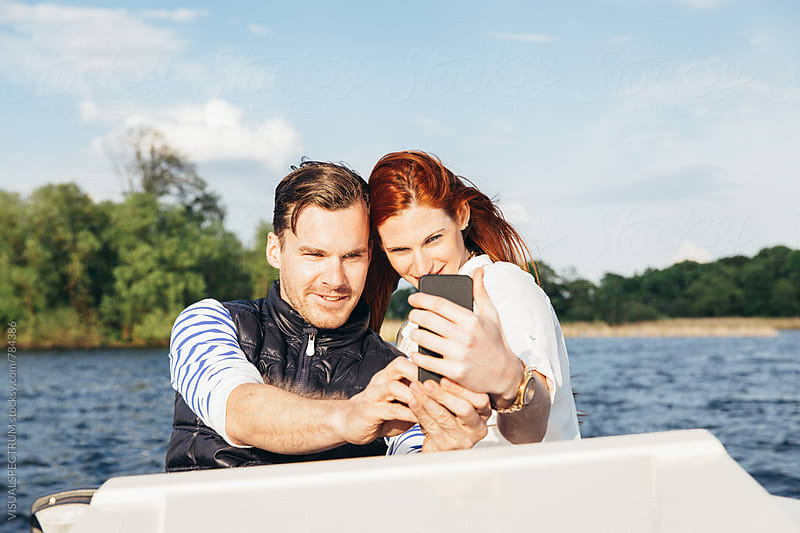 Caucasian Couple Taking Selfie With Cellphone on Motorboat by Julien L. Balmer for Stocksy United