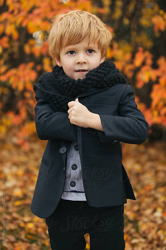 A young boy reaching into the inside of his black blazer looking away by Ania Boniecka for Stocksy United
