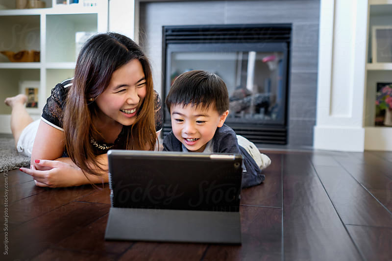 Asian boy watching on his tablet with his mother at home by Suprijono Suharjoto for Stocksy United