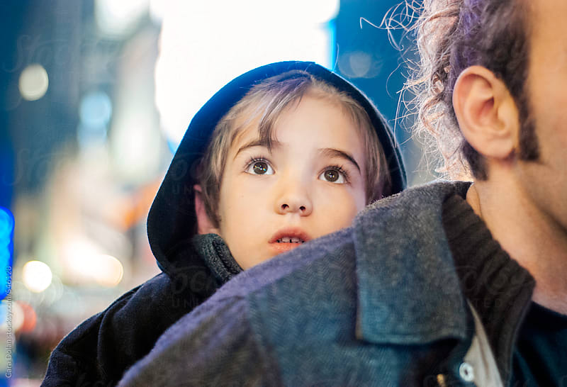 Child rides on his father's back as they walk through Times Square by Cara Dolan for Stocksy United