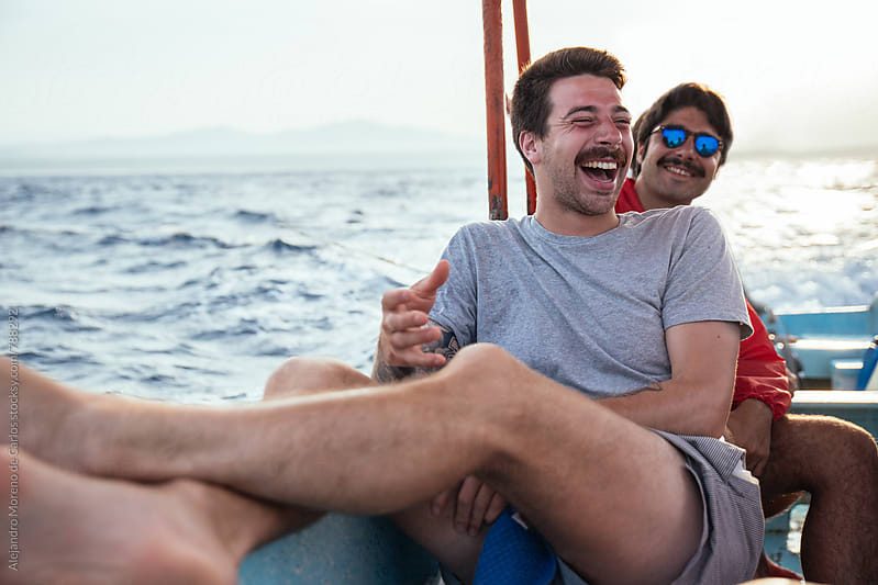 Young men laughing and having fun during a boat trip in the sea by Alejandro Moreno de Carlos for Stocksy United
