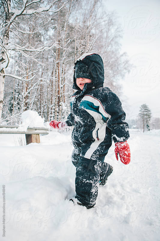 Boy Playing in Snow by Stephen Morris for Stocksy United