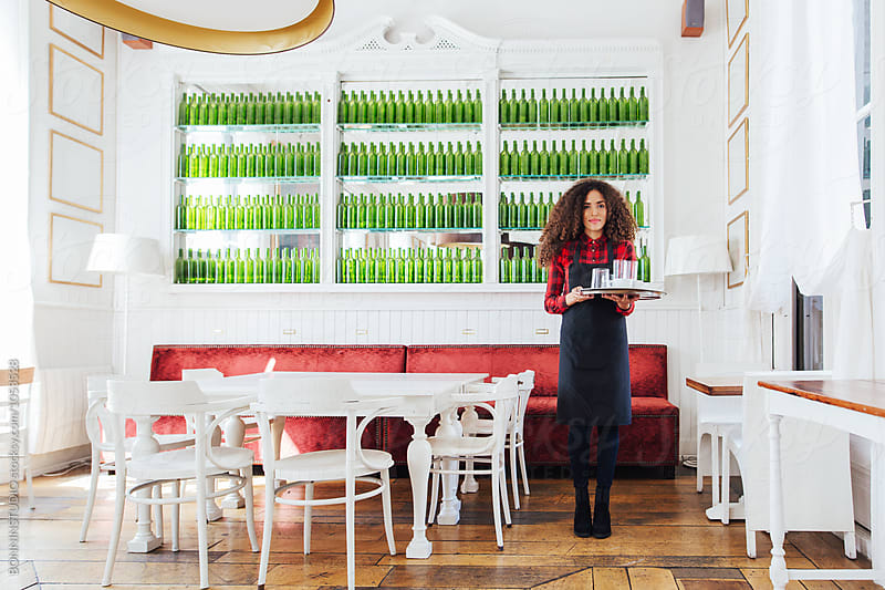 Young female wearing an apron holding a tray with coffee in a beautiful coffee shop. by BONNINSTUDIO for Stocksy United
