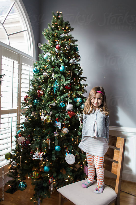 Cute young girl hanging christmas ornaments by Jakob for Stocksy United