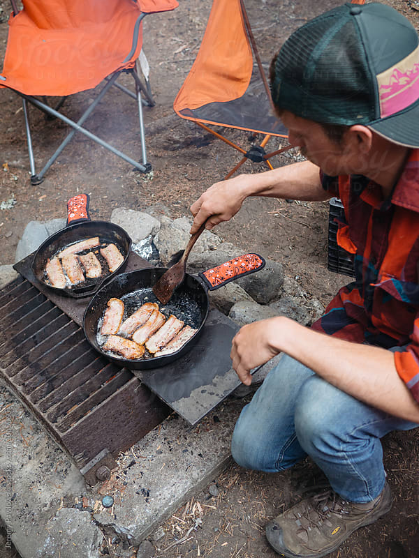 Young man flipping sizzling bacon while cooking with cast iron on campfire by Jeremy Pawlowski for Stocksy United