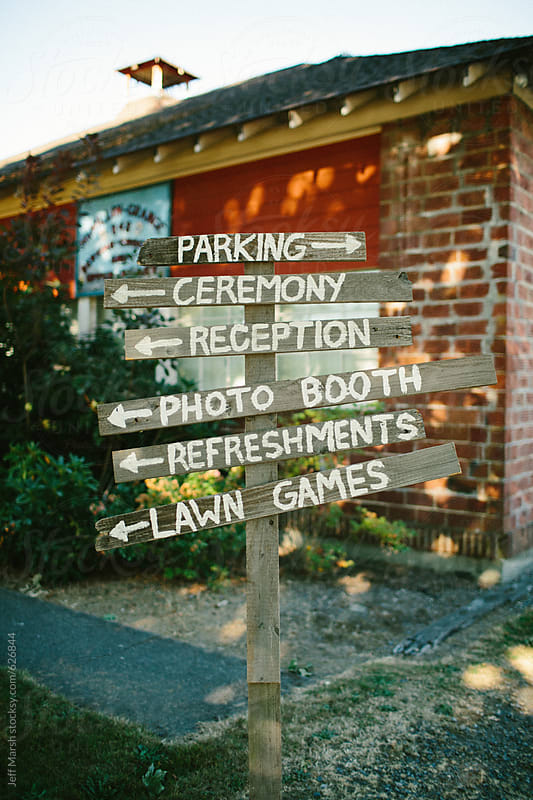 Directional sign at a wedding by Jeff Marsh for Stocksy United