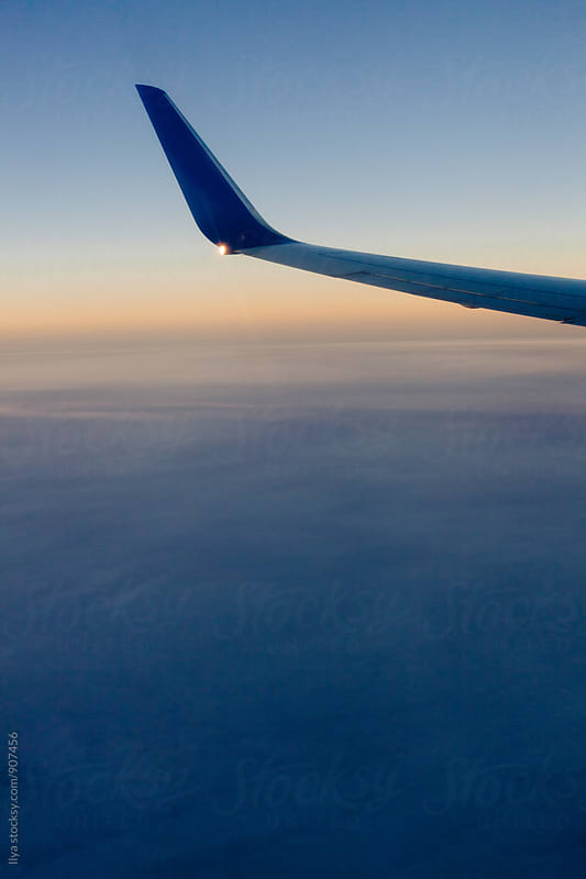 Airplane flying over sunset - view of the wing from the window by Ilya for Stocksy United