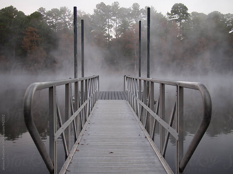 Metal dock in the morning fog on a lake by Jeremy Pawlowski for Stocksy United