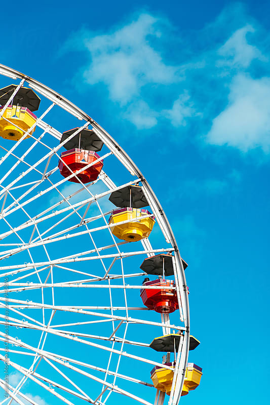 Detail of colourful ferris wheel against blue sky. Vertical by Alejandro Moreno de Carlos for Stocksy United