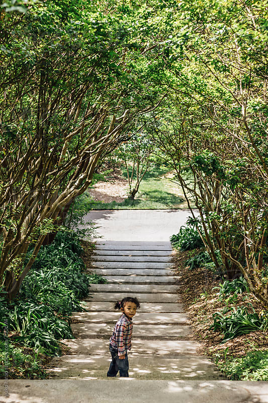 Little Asian girl, standing under tree tunnel by yuko hirao for Stocksy United