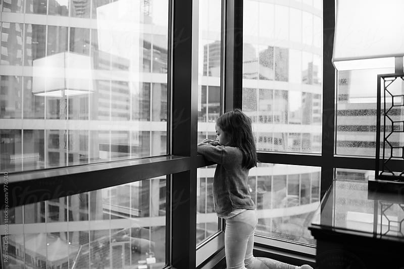 Little Girl Looking Out Apartment Window by Ronnie Comeau for Stocksy United