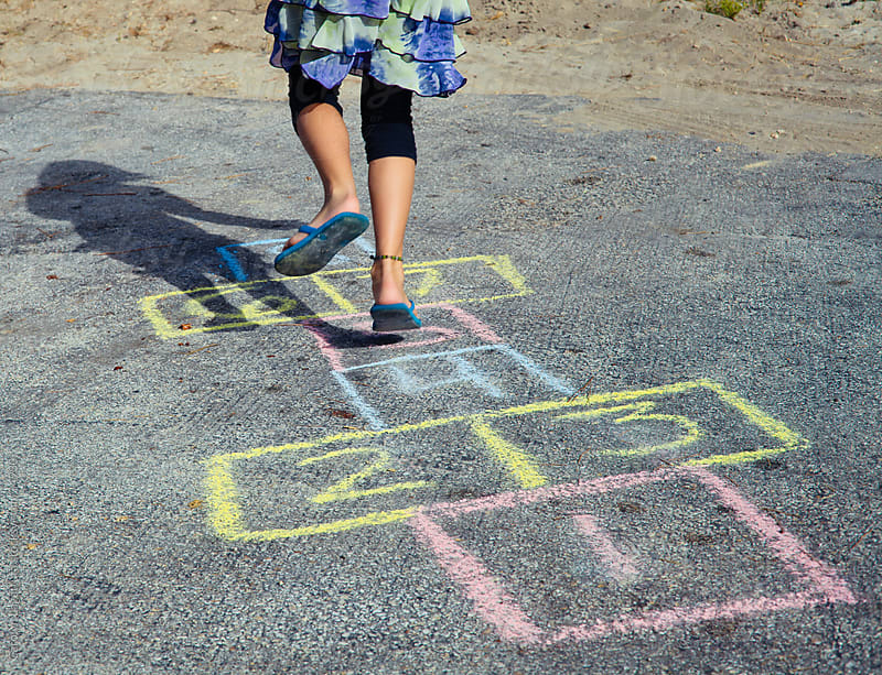Young girl in a skirt and leggings jumping along a chalk hopscotch drawing. by Carolyn Lagattuta for Stocksy United