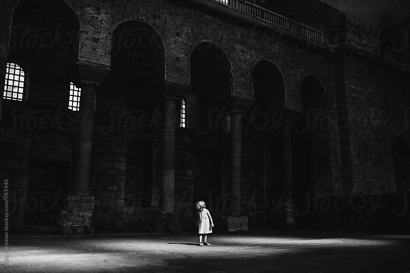 Little girl looks down at her shadow in a large, dark historical building. by Julia Forsman for Stocksy United