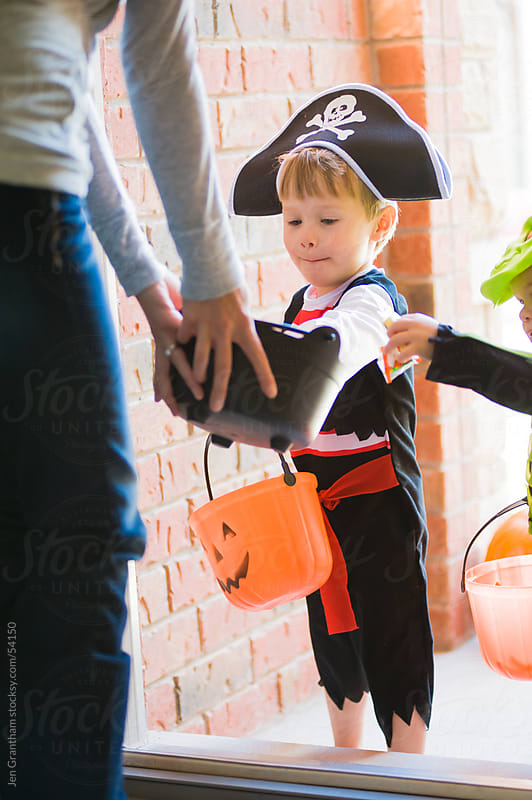 Toddler trick-or-treating in pirate costume by Jen Grantham for Stocksy United