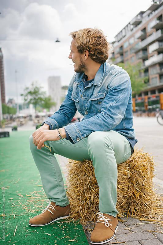 Blond man sitting on a hay bale in the middle of Rotterdam by Koen Meershoek for Stocksy United