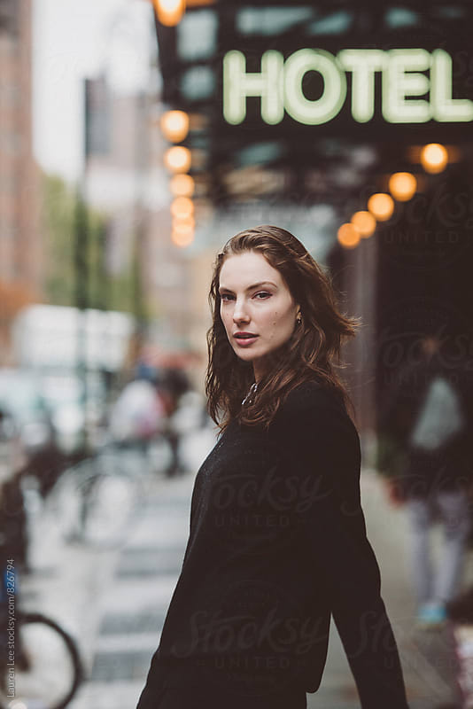 Young woman in the street by a hotel by Lauren Naefe for Stocksy United