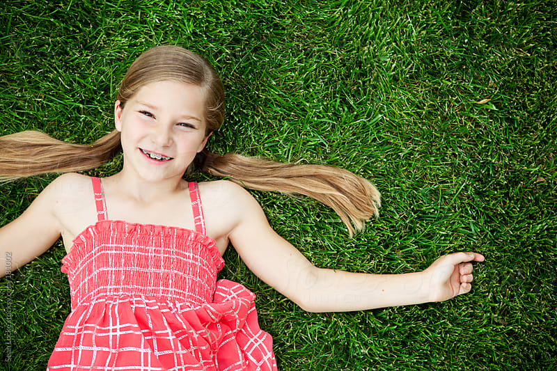 Grass: Cute Young Girl Lying Back on Grass by Sean Locke for Stocksy United