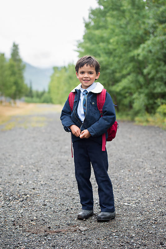 smiling boy zips his jacket before walking to school by Tara Romasanta for Stocksy United
