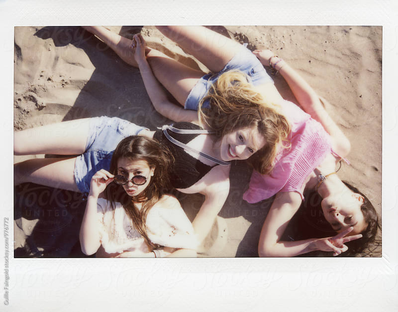 Instant photo of three girlfriends on sandy beach by Guille Faingold for Stocksy United