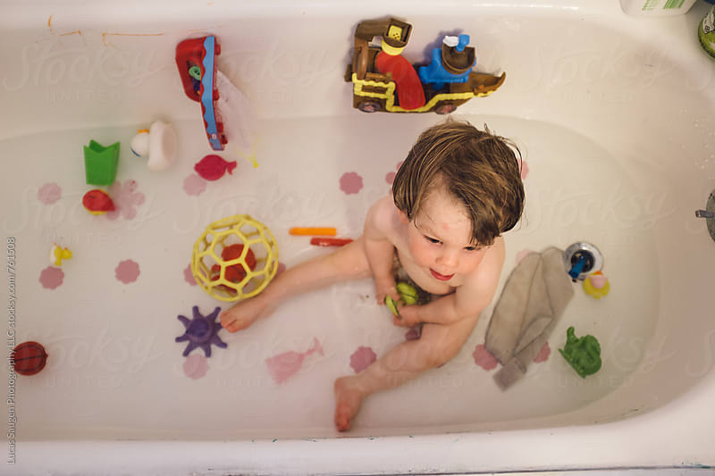 A young boy in a tub surrounded by bath toys. by Lucas Saugen for Stocksy United