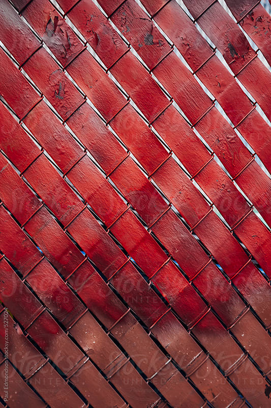 Red paint covering chain-link fence by Paul Edmondson for Stocksy United