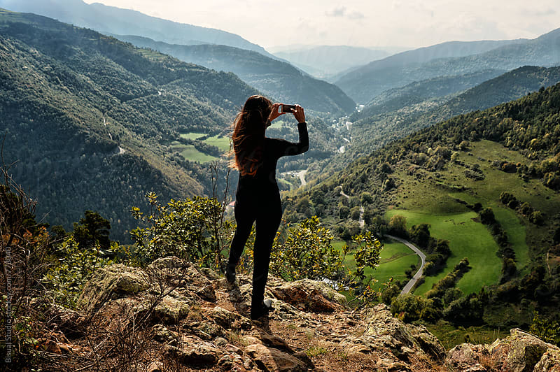 Woman taking pictures with the phone on the top of a mountain by Bisual Studio for Stocksy United