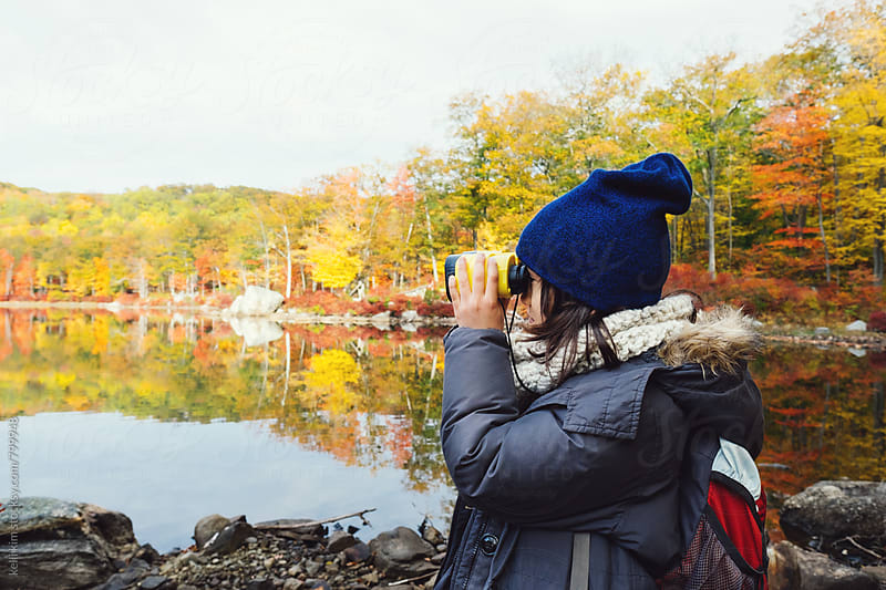 Young boy peers out at lake through binoculars by kelli kim for Stocksy United