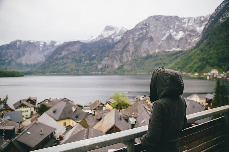 Rear view of traveler in coat hood enjoying tranquil view of mountain village at lake by Andrey Pavlov for Stocksy United