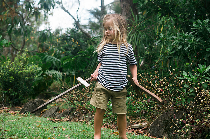 Child with long hair and stripy shirt playing with two wooden swords in bushy back yard  by Tahl Rinsky for Stocksy United