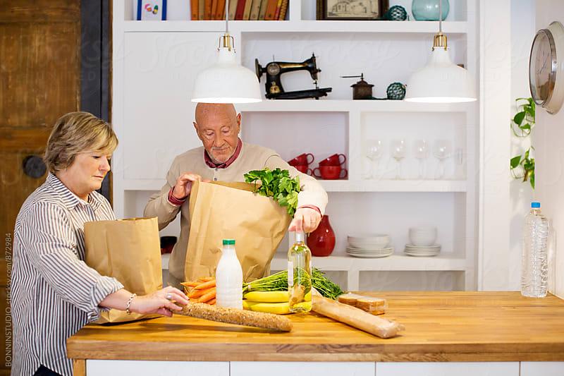 Elderly couple unpacks healthy market food in their kitchen. by BONNINSTUDIO for Stocksy United
