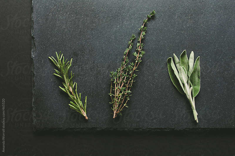 Rosemary, thyme, and sage lined up on a slate background by Amanda Worrall for Stocksy United