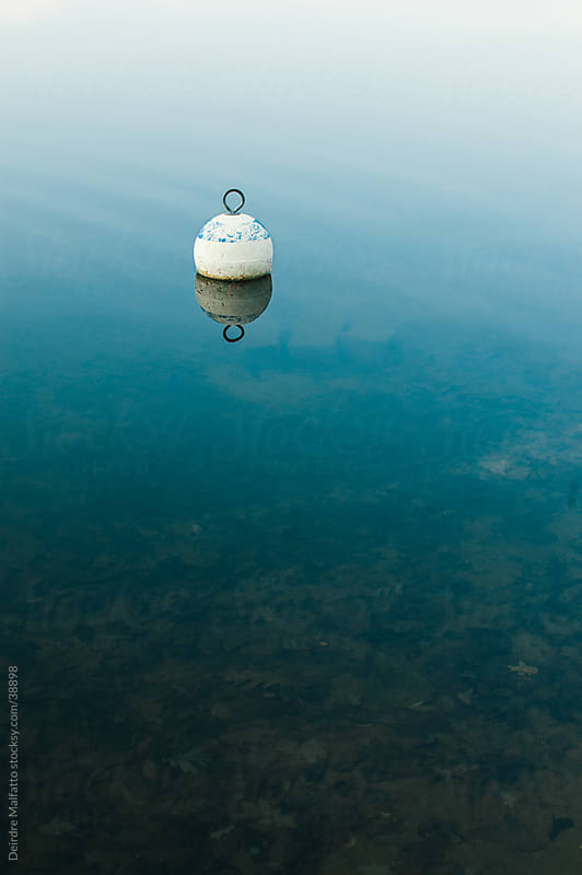 Wooden buoy floating on water surface by Deirdre Malfatto for Stocksy United
