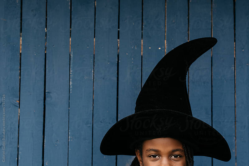 Smiling African American girl wearing a witch hat for Halloween by Gabriel (Gabi) Bucataru for Stocksy United