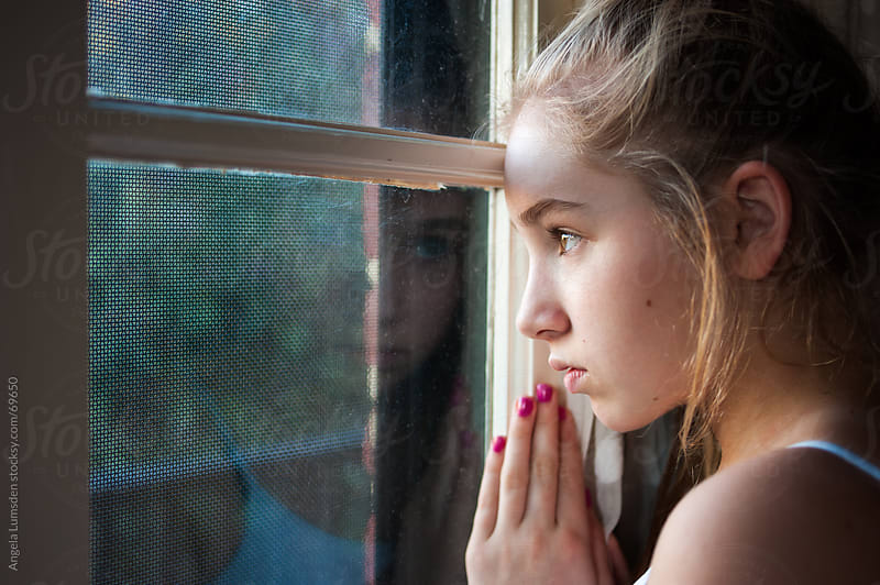 Girl looking out a window by Angela Lumsden for Stocksy United