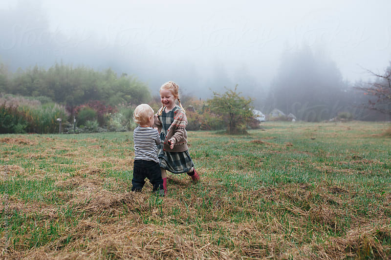 A young brother and sister run to each other in a foggy field by Amanda Voelker for Stocksy United