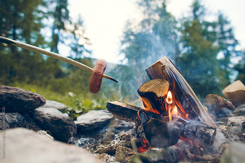 Grilling  a sausage on a stick above a bonfire in the woods by Denni Van Huis for Stocksy United
